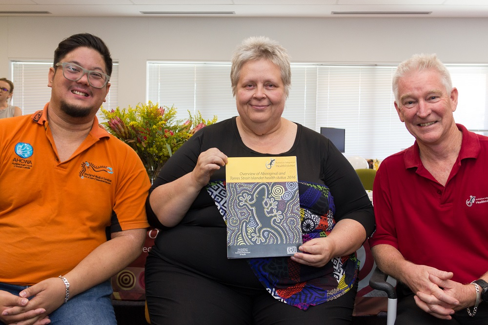 : L-R James Harris, Sharon Bushby (AHCWA) and Neil Drew (HealthInfoNet Director) pictured holding the 2016 Overview at the HealthInfoNet's Close the Gap day event.